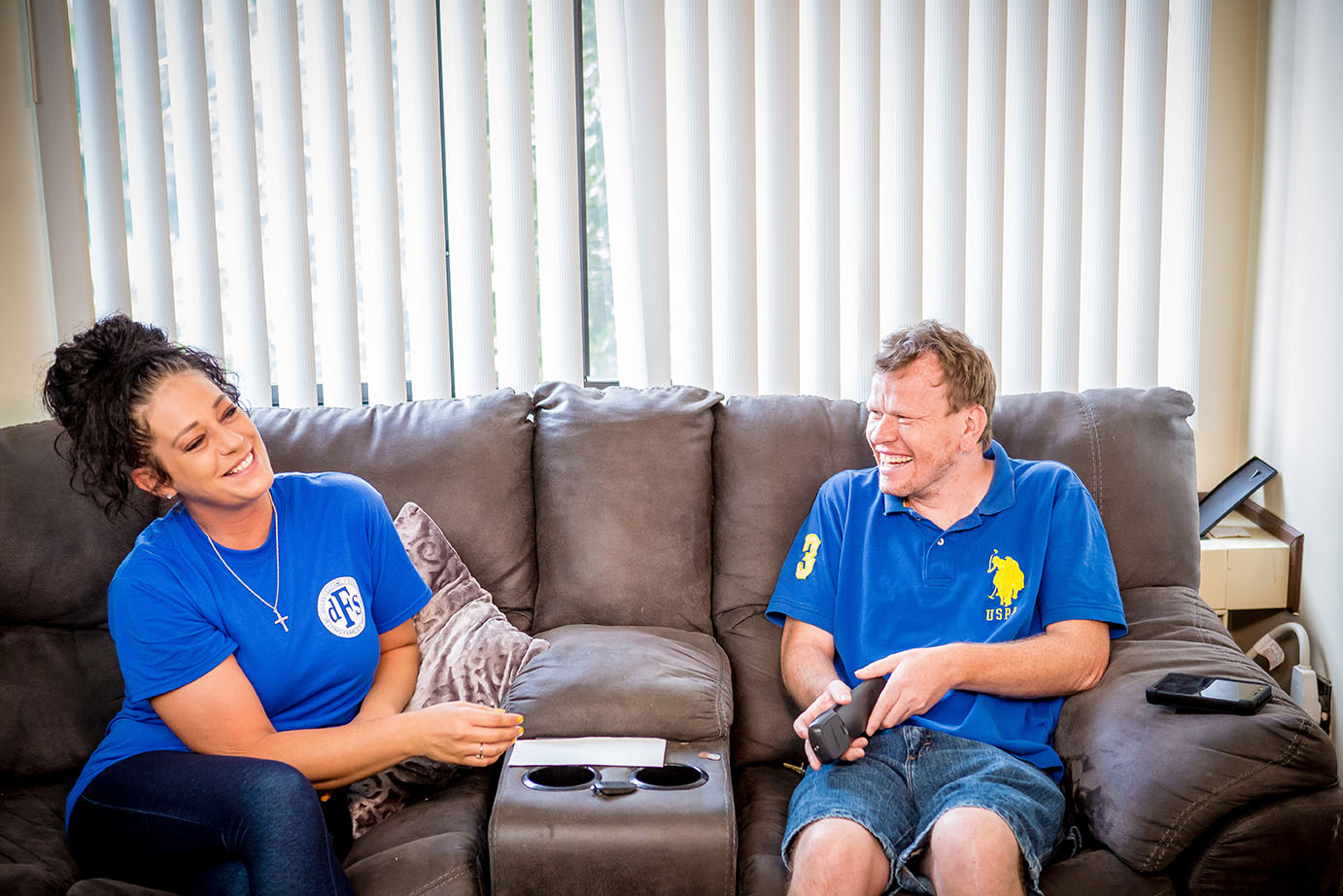 Man and woman smiling on couch talking