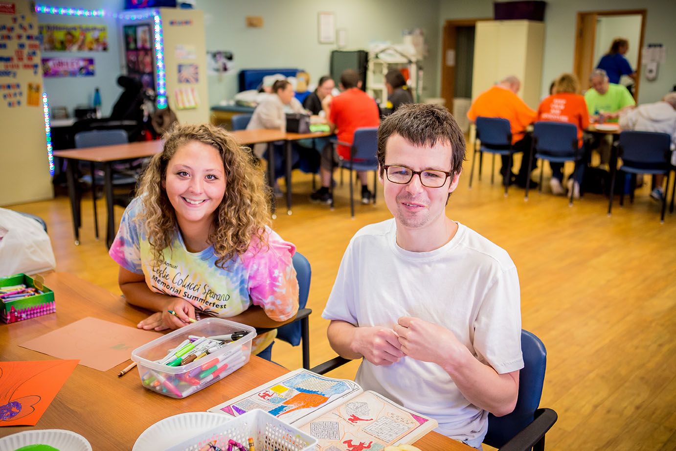man and woman sitting at table smiling doing crafts