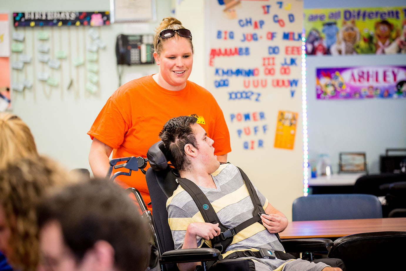 person in wheelchair with helper